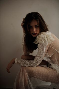 Daydreaming beauty in a lovely sheer and lace white dress.