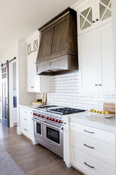 A Wolf dual range sits between white shaker cabinets accented with oil rubbed bronze pulls and a white quartz countertop fixed against white linear backsplash tiles with dark grout beneath white shaker cabinets stacked beneath glass front cabinets flanking a dark stained hood.