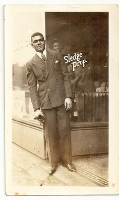 Posed in front of barbershop -- Do you think this might be Mr. Sledge, the Proprietor himself? I like how the man inside the building echoes his pose. Anybody know the source? My Black Is Beautiful, Black Love, Black And White, Vintage Black Glamour, Vintage Men, Afro, American Photo, Handsome Black Men, Historical Pictures