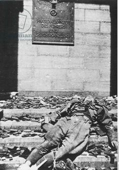 The dead body of a German officer lying on the steps of the Reich Chancellery following the Battle of Berlin, May 1945 (b/w photo)