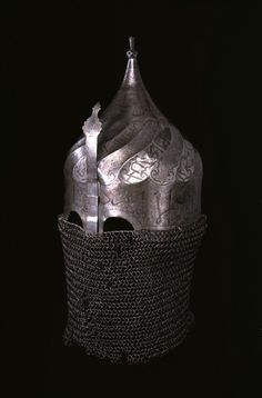"Helmet with Neck Guard of Mail and Nose Guard ca. 16th century  Helmets like this, that have preserved their original chain-mail ""aventail,"" or face and neck covering, have been likened to masks that conceal the face and create a sense of mystery. Their primary function, however, was to protect the wearer.  Islamic helmets often were decorated with inscriptions that invoke God's power and blessing. Sometimes, as here, the writing cannot be easily deciphered and may even be meaningless."