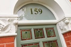 Victorian part-glazed green front door with seven panels, textured and stained glass detail and chrome door furniture.