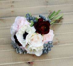 Inspired for a softer color scheme, this winter wedding bouquet compliments a blush and navy wedding perfectly! Includes: - White Anemone - Plum Ranunculus - Blue Berries - Blush Roses - Grey Dusty Mi