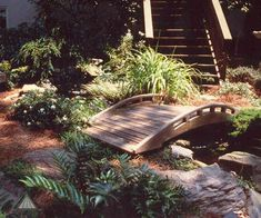 A low-profile, asian-inspired bridge makes for a nice purposeful accent through a backyard garden and over a small stream. Designed and built by Atlanta Decking.