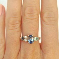 Custom stone cluster ring with a blue and white bicolor Sri Lankan sapphire accented by paraiba tourmaline (the bright green stone), antique red coral, white diamonds and another dark blue bicolor sapphire. Set in 14k yellow gold. Mociun