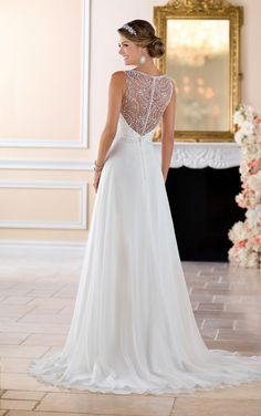 From Stella York, this beaded high neck wedding dress is a fresh, fashion forward bridal look with a timeless twist. Capri chiffon over Lavish satin in a casual column silhouette with an ornately beaded neckline is both comfortable and stylish. The scroll pattern in the bead work helps to highlight and define the waist, while the chiffon skirt is breezy and cool-perfect for a wedding beach or an outdoor venue! The beading continues on the open back, while the skirt leads into a modest…