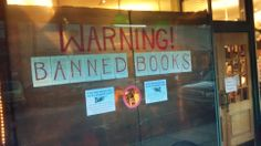 "Banned Books display at Annie Bloom's Books in Portland, OR. Most of the window was blacked out with trash bags, leaving a peephole to look through. The smaller signs read ""We advise children and sensitive individuals to take caution, lest they be exposed to ideas that other people find questionable."""