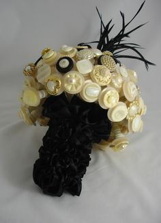 This is a dazzling eyecatcher, made up of 100 stems, its a feast for your eyes, its topped with huge sparkling bling buttons, diamonte buttons, faux pearl buttons and much more.  A spray of black goose feathers, and black stones give it a dark, dramatic look.  The handle of the bouquet is a very full ruffle handle.  You may have a brooch or piece of jewellery of your own that can be incorporated into your Letters4lilly bespoke wedding bouquet.