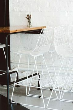 mur blanc de briques, chaise en fer blanc, table haute de cuisine en bois, table salle a manger