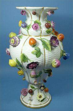 Meissen Vase. Alexandra Alfandry - The large Vase is Meissen, c. 1880 with applied flowers and fruit on a basket pattern background, c. 48 cm high. Meissen c. 1910.
