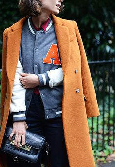 who says you can't layer a coat over a  varsity jacket | It List