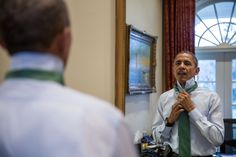 President Barack Obama puts on a green tie in observance of St. Patrick's Day, in the Outer Oval Office, March 17, 2015. (Official White House Photo by Pete Souza)