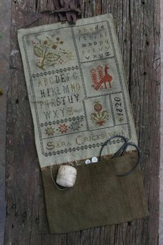"""From Stacy Nash Primitives is this cross stitch pattern titled """"Sara Cricks Pocket Roll"""" that is stitched with DMC threads. The primitive s..."""
