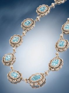 An Edwardian cushion-shaped aquamarine and diamond cluster necklace in the garland style, mounted in silver and gold, in fitted case by London & Ryder. Source: Humphrey Butler 2012-13 catalogue.
