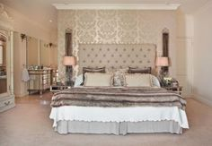 Very glam bedroom with interesting colours and textures from metalic wallpaper to faux throw to salmon coloured lamp shades