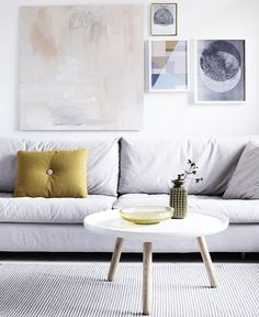 White scandinavian style lounge room. white couch, white coffee table and art wall. At Hermans - Blog - New Beginnings