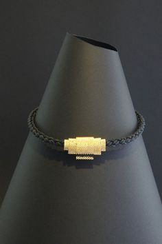 A Strip of Black (Peyote stitch of Gold Miyuki Beads on a thick leather cord. )