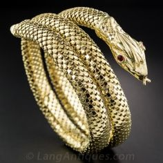 Supple and slinky, this gleaming Cleopatra worthy serpent bracelet is composed of 18K springy tubular mesh adorned with an intrinsic scalar pattern. Ruby red glass eyes. Coiled and ready to strike!