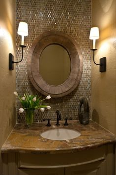 Love the light and sparkle the tile brings to this bath.  Also like that they contrasted the tile with a more rustic mirror.  I would have probably done a boring black framed mirror to match the style of the sconces.