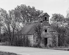 A rustic old one room school with an added on belfry in rural Kansas