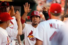 St. Louis Cardinals' Jon Jay, center, is congratulated by teammates after scoring on an RBI double by Matt Holliday during the third inning ...