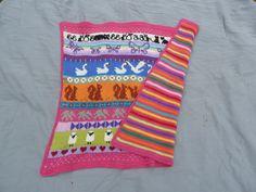 Babytæppe, mønster på uld side og striber på bomuldsside.