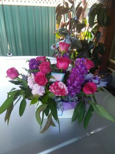 A purple and pink themed arrangement in pretty white tin.