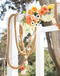 18 Wedding Arches That Set the Scene for Romance: Nautical Knots. A wood structure was painted white and draped with thick rope picked up from a shipyard. Clusters of flowers were affixed to the top, with dainty blooms fastened to the asymmetrical rope.