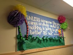 Dr Seuss Week Bulletin Board. Loved this board! I made trees from tissue paper (watched tissue paper flower tutorial on YouTube) Trunks I bought at the dollar store (long tubes kids whip around and they whistle) then I used electrical tape to create black stripes on them. I cut wording and Lorax on my cricut. Lorax body I used the monster body from paper doll cartridge and just cut off antenna. Arms are just cut from paper doll body. Drew and cut out mustache on yellow card stock. - Tanya…