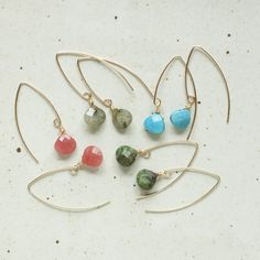 """Simple but trendy and stylish with arched ear wires in 14K Gold Filled. Delicate gold wires thread and dangle for a simple delicate look. 8 colors to choose from: Howlite (blue turquoise look), Labradorite, Green Turquoise, Strawberry Jade, Mother of Pearl, Opalite, Onyx, and Crystal Quartz. - Wire measures 7/8"""" in the front, 1 1/2"""" in the back - 14K Gold Filled Wire Wire - Proudly handcrafted in our studio in Portland, Oregon"""