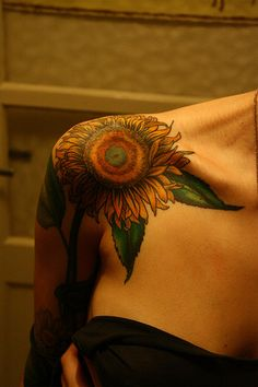 This sunflower tattoo is placed on the round bone of the shoulder, accentuating that area of the body