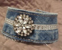 This cuff bracelet has been constructed from a wash denim waistband. The bracelet measures approximately 8 inches long when fastened and about 1