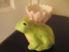 frog egg cup holding a flower