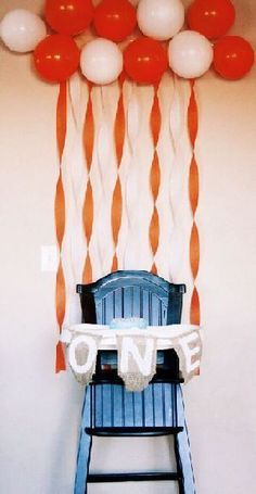 Balloons and streamers tied to a highchair for 1st birthday.  See more first boy birthday decorations and party ideas at one-stop-party-ideas.com
