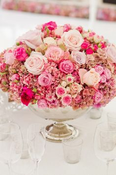 Low flower arrangement in shades of pink with a variety of roses for the wedding reception
