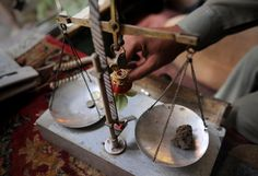 Pakistan's War On Drugs | This photograph taken on May 31, 2012 shows a Pakistani drug dealer weighing hashish at his shop in northwestern city of Peshawar. (A. MAJEED/AFP/Getty Images)