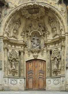 Recessed entry to the cathedral in San Sebastian, Spain, has beautiful carvings in the alcove with a massive wood carved door.