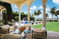 Outside of the living room are this loggia and pool deck where Brown Jordan chaises edge the pool and two of four sculptures frame views of the Intracoastal Waterway. The pool is lined in indigo mosaic ceramic tile to lend continuity with the interior color scheme.