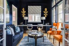 EJ Interiors - living rooms - navy walls, gold accessory, blue sofa, glass coffee table, pattern, abstract art, orange accent,  Dallas sitti...