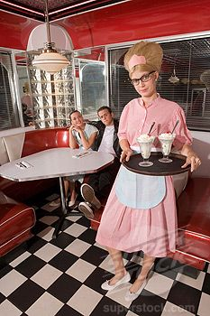 Waitress in 1950s style uniform serving ice cream sundaes to couple in diner (1785-7950 / GPM0185K0705 © Kablonk)