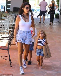 Mommy's little helper: Penelope was seen carrying one of the shopping bags as the family navigated their way through the shopping center