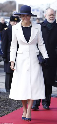 Crown Princess Victoria of Sweden looked elegant in a white coat that accentuated her slim waist as she attendeda memorial service for the Swedish Volunteer Corps