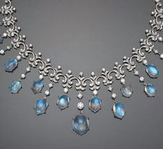 A moonstone and diamond necklace of fringe design; estimated total moonstone weight: 49.50 carats; estimated total diamond weight: 4.95 carats; mounted in eighteen karat white gold; length: 16 1/4in.