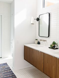 Mid Century Modern Bathroom Design. Floating Walnut Vanity from Kohler, Wall Mounted Sinks with Brushed Nickel Finish, Sconces and Stacked 2x8 Tile in white and Green.