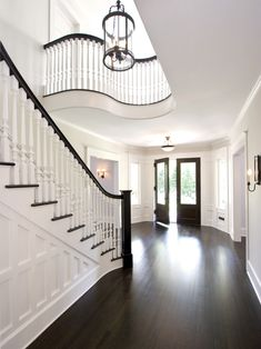 I love how the dark wood stair railing and balustrade compliment the dark wood door and floors-Entry Foyer Design,