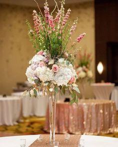 Tall centerpieces filled with larkspur roses and hydrangeas set the scene at the Renaissance Baton Rouge wedding reception.  Photography by @genovese_ashford  #batonrougewedding #nolaweddings #bridetobe2017 #bridetobe #blushwedding #receptioncenterpiece #floralcenterpiece #louisianawedding #batonrougebride