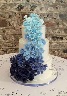 3 tier white wedding cake with blue ombre flower cascade. The flowers were roses, lisianthus and hydrangea. 3 Tier Wedding Cakes, Wedding Cake Prices, Floral Wedding Cakes, Amazing Wedding Cakes, White Wedding Cakes, Wedding Cake Designs, Bolo Floral, Belle Cake, Wedding Cake Fresh Flowers