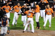 J.J. Hardy #2 of the Baltimore Orioles is mobbed by teammates after scoring the game winning run in the tenth inning against the Houston Astros.