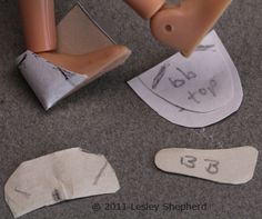 Paper is fitted over the heel of a doll's foot and the front of the heel section where the toe meets the heel pattern is marked.