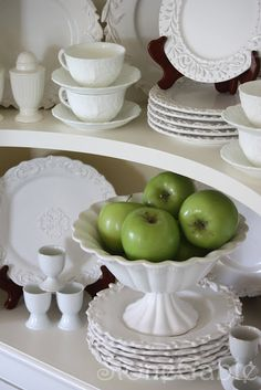 White dish display in an open corner cabinet.